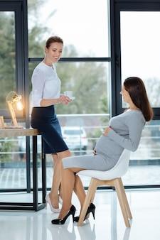Быть позитивным. веселые коллеги в полный рост пьют чай, выражая волнение