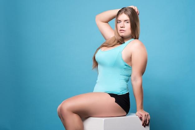 Быть сексуальным. привлекательная молодая пухлая женщина сексуально позирует сидя