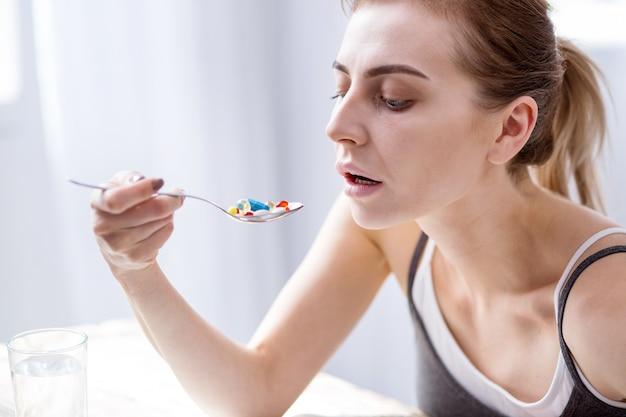 Будучи болен. грустная молодая женщина смотрит на таблетки, держа ложку