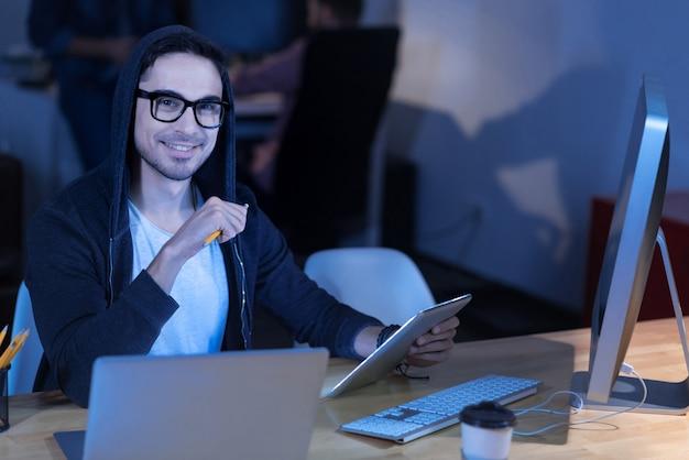 기술에 집착하는 것. 현대 기술로 작업하면서 웃고 태블릿을 사용하는 지능형 행복 잘 생긴 남자