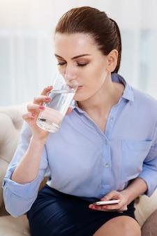 のどが渇いています。肘掛け椅子に座ってグラスと飲料水を保持している魅力的な自営業のプロの女性