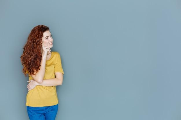 思いやりがある。ほっぺたに触れながら笑顔で脇を向いて元気に喜んでいる素敵な女性