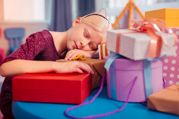 Being tired. cute kid keeping eyes closed while sleeping after party