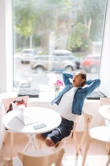 疲れている。カフェのテーブルに座っている間彼の首に触れるハンサムな国際的な男