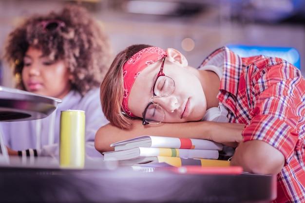 Усталость. расслабленный белокурый мальчик с закрытыми глазами мечтает о праздниках