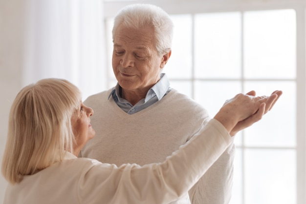 Being together. nice handsome aged man looking at his wife and smiling while dancing with her