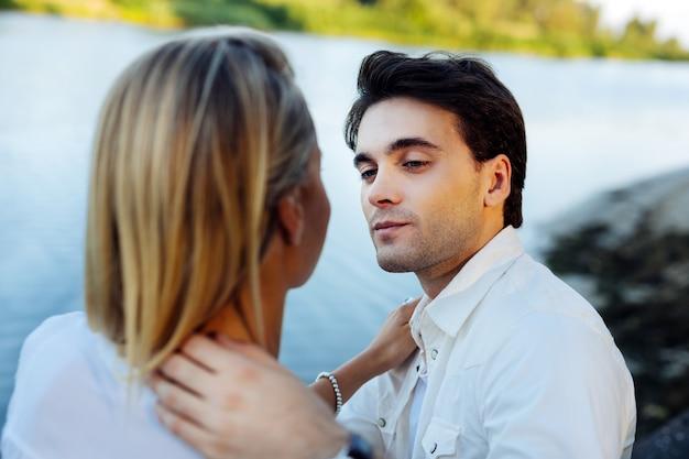 一緒にいます。ロマンチックなデートを楽しみながらお互いを見つめる素敵な若いカップル