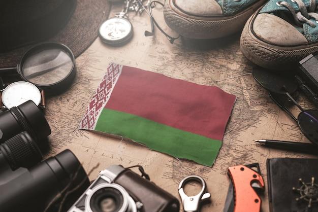 Флаг беларуси между аксессуарами путешественника на старой винтажной карте. концепция туристического направления.