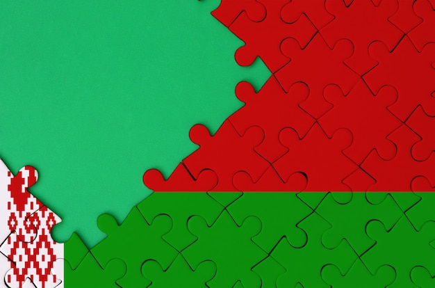 Belarus flag  is depicted on a completed jigsaw puzzle with free green copy space on the left side