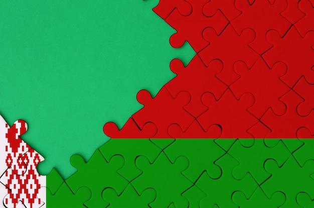 벨로루시 깃발은 왼쪽에 무료 녹색 복사 공간이있는 완성 된 직소 퍼즐에 그려져 있습니다.