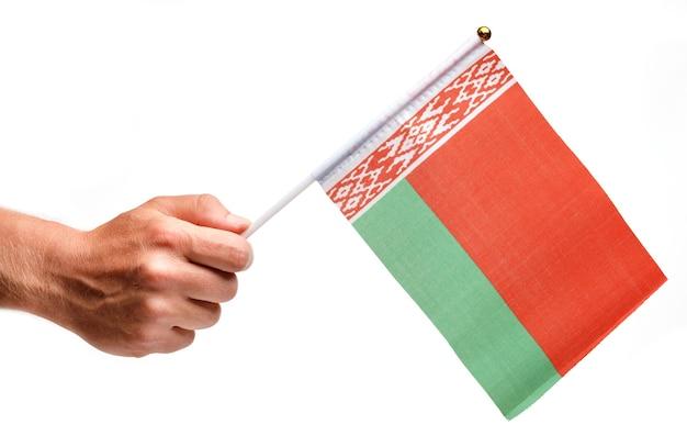 Белорусский флаг небольшой в руке изолировать.