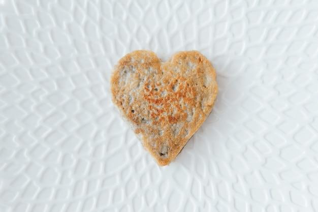 벨로루시 국가 요리-감자 팬케이크. 아름다운 하얀 접시에 심장 모양입니다.