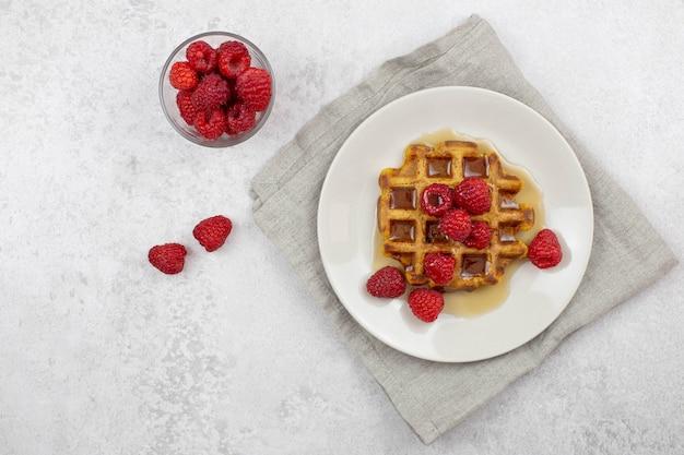 메이플 시럽을 곁들인 벨기에 당근 와플과 회색 콘크리트에 신선한 나무 딸기