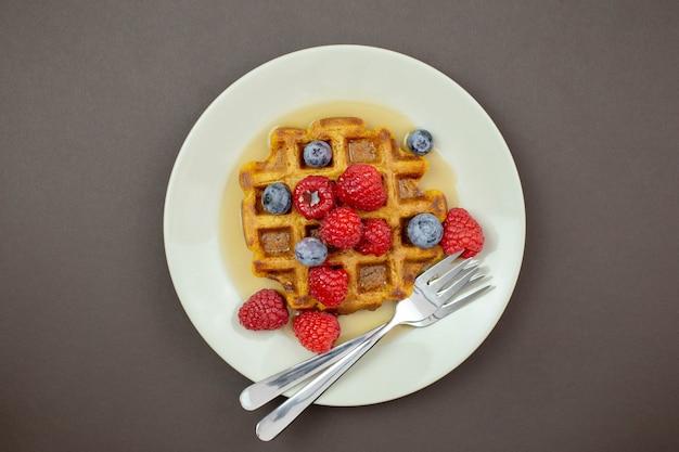 메이플 시럽, 신선한 나무 딸기와 어두운 배경에 블루 베리와 벨기에, 당근 와플.