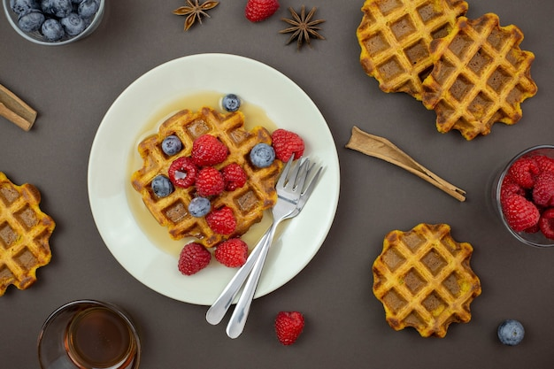 Belgian, carrot waffles with maple syrup and fresh raspberries, blueberry, cinnamon and star anise on dark background.