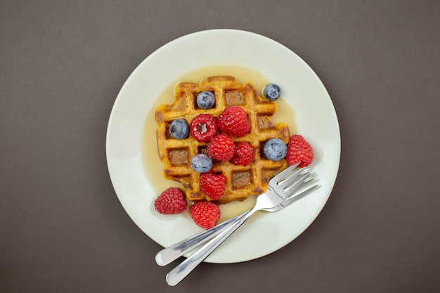 Belgian, carrot waffles with maple syrup, fresh raspberries and blueberry on dark background.