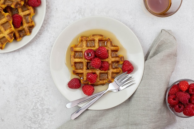 Belgian, carrot waffles with maple syrup and fresh raspberries on gray background.