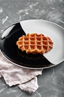 벨기에 또는 미국 와플, 맛있는 달콤한 요리, 검은 색과 흰색 접시에 디저트 스낵 메뉴 개념