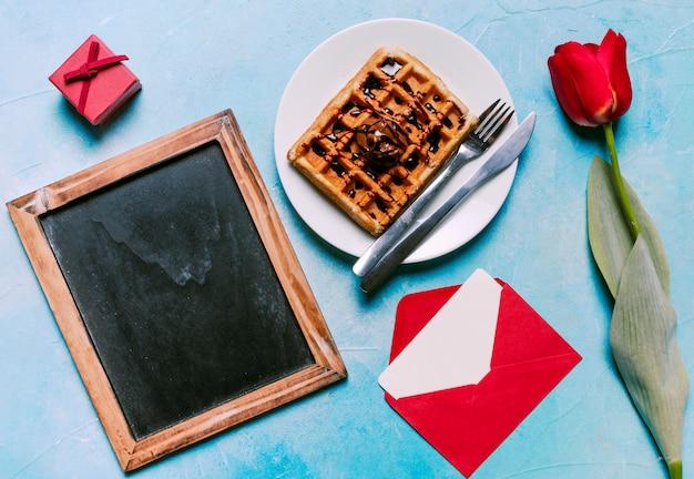 Belgian waffle on plate with blank chalkboard