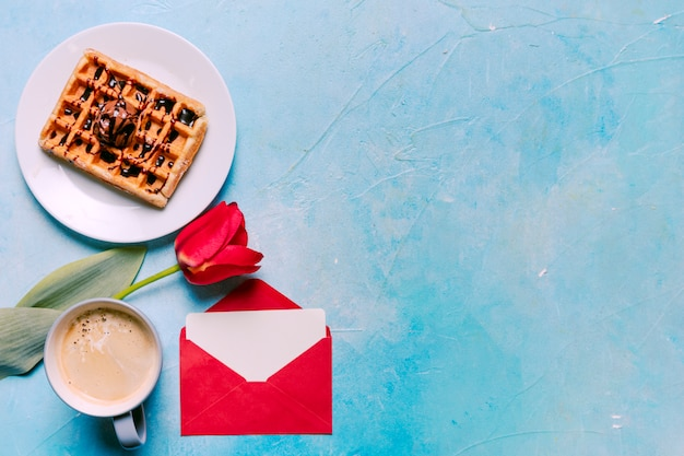 Belgian waffle on plate with red tulip