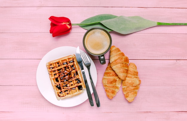 Belgian waffle with coffee and tulip on table