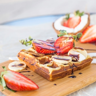 Belgian waffle with fruit and chocolate sauce is beautifully served on a wooden board