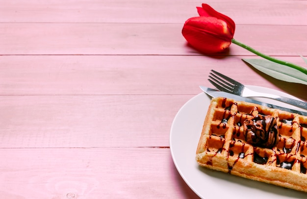 Belgian waffle with red tulip on table