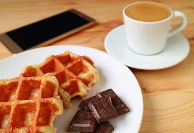 ベルギーワッフルとダークチョコレートチャンク、背景がぼやけたホットコーヒーとスマートフォン