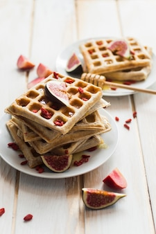 Belgian waffles and fig fruit served in white plate with honey dipper on wooden table