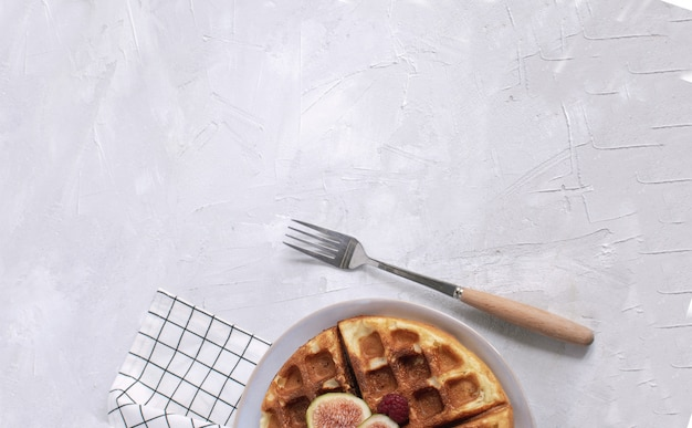 Belgian waffles  figs raspberries honey espresso coffee white wooden background flat lay