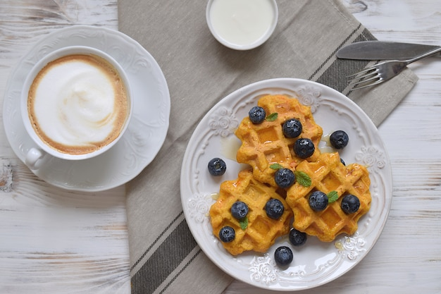 Belgian waffles healthy breakfast  blueberry honey mint sour cream cappuccino coffee white wooden  top view flat lay