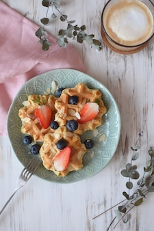 Belgian waffles healthy breakfast  blueberry strawberry cappuccino coffee white wooden  eucalyptus branch top view flat lay