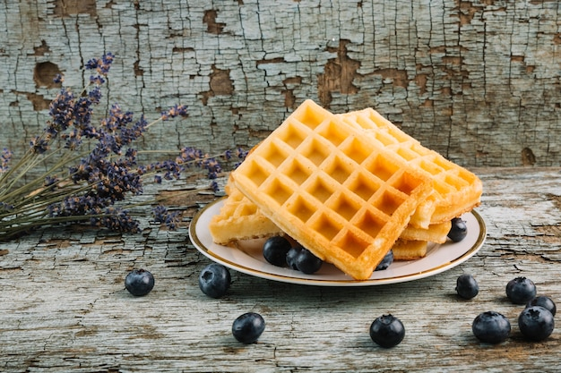 Belgian waffles near blueberries and bouquet