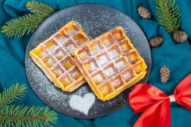 粉砂糖を振りかけた黒い皿にベルギーワッフル。クリスマスと新年の気分。赤いリボン、コーン、緑の布の松の枝。上面図