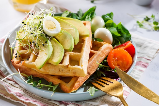 Belgian waffles with avocado, eggs, micro green and tomatoes with orange juice on marble table.