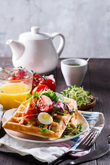 Belgian waffles with avocado, eggs, micro green and tomatoes with orange juice and tea on wooden table