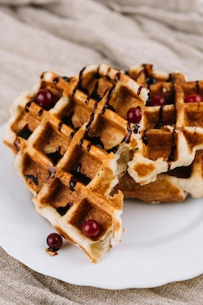 Belgian waffles with berry and chocolate syrup on white plate