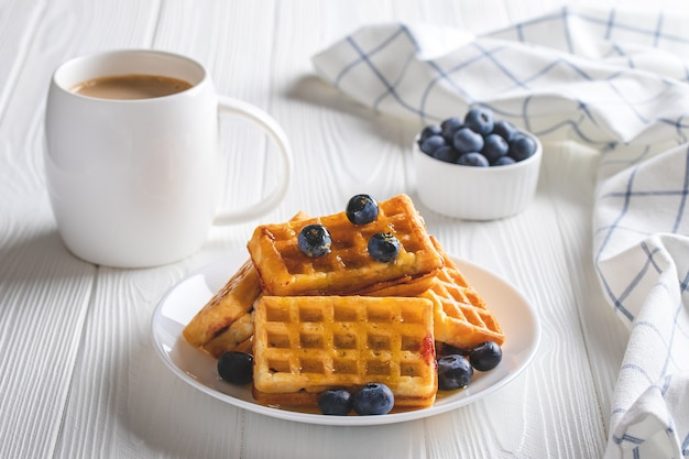 Belgian waffles with blueberries and coffee on a wood table