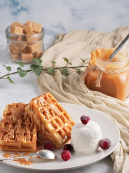 Belgian waffles with caramel, berries and ice cream. homemade waffles with delicious caramel sauce on a plate