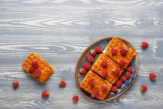 크림과 신선한 나무 딸기와 벨기에 와플.