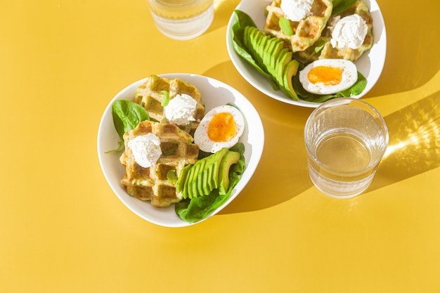 Belgian waffles with cream cheese egg and avocado in a white plate healthy breakfast