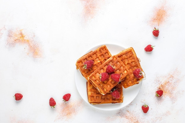 Belgian waffles with cream and fresh raspberries.