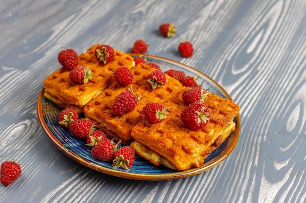 Waffle belgi con panna e lamponi freschi.