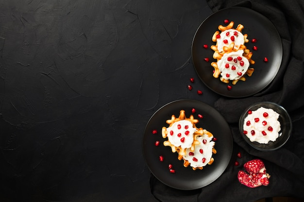 Belgian waffles with cream and pomegranate seeds on black