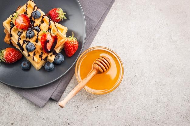 꿀, 초콜릿, 딸기, 블루 베리, 메이플 시럽, 크림을 곁들인 벨기에 와플.