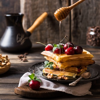 Belgian waffles with honey and powdered sugar. cherries. coffee beans in jar. turkish coff
