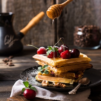 Belgian waffles with honey, powdered sugar. cherries. coffee beans. turkish coffee pot for