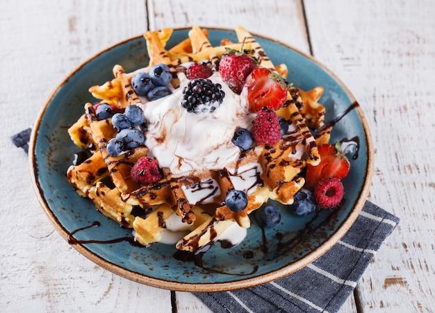 Belgian waffles with ice cream,fresh berries and chocolate sauce.