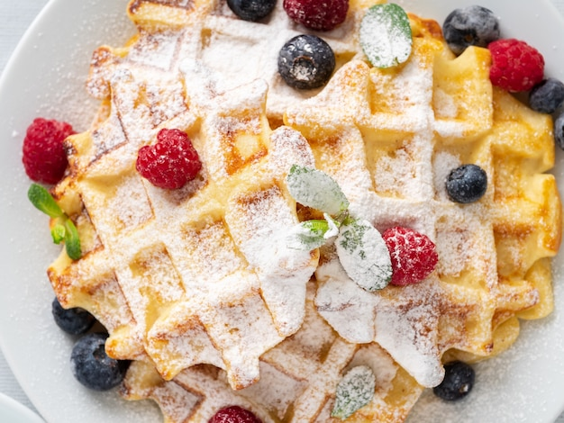 Belgian waffles with raspberries, blueberries, curd, close-up, top view. healthy homemade breakfast