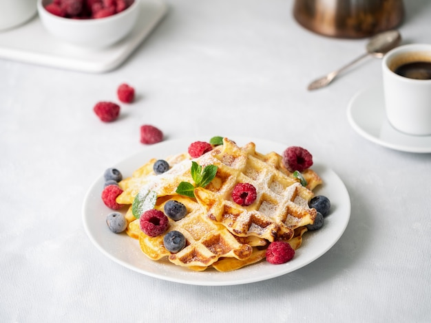 Belgian waffles with raspberries, blueberries, curd and coffee, side view. healthy breakfast